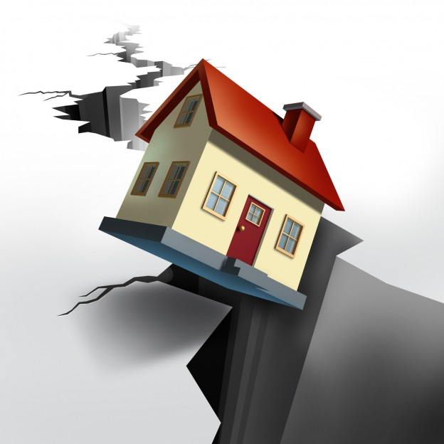 Falling real estate prices and housing market decline with earthquake cracked  floor showing a huge hole in the ground and a model home that is descending  and sinking into the black hole of debt and foreclosure.