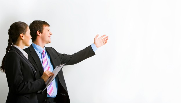 Portrait of businessman pointing at wall with assistant near by